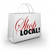 image of encouraging  - The words Shop Local on a white shopping bag encouraging you to support your local community or hometown by buying merchandise in your backyard and keeping money nearby - JPG