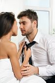 stock photo of intimate  - Beautiful sexy Intimate couple girl takes off his tie out of a guy - JPG