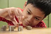 stock photo of pesos  - A photo of a boy looking at a stack of coins and stacking them - JPG