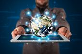 stock photo of presenter  - Young businessman presenting 3d earth globe in tablet  - JPG