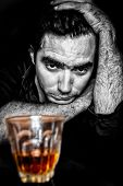 Black and white grunge portrait of a drunk and depressed hispanic man (with a contrasty golden alcoh