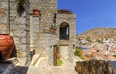 picture of hydra  - Some local architecture on the hills of the Greek island Hydra and a view of the sea and houses on the background - JPG