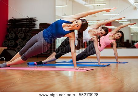 Side plank yoga pose by three women poster