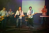 Five men with musical instruments performs on stage in a club