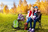 stock photo of 11 year old  - Two happy smiling laughing and hugging girls 11 years old sitting on the bench in autumn park - JPG