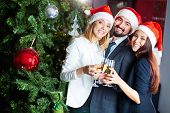 Portrait of joyful colleagues in Santa caps toasting with champagne by Christmas tree