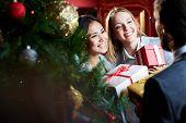 Portrait of joyful females giving xmas presents to their associate