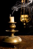 Blown out candle in antique candle stick and in the background a blurred incense thurible