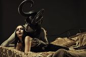 stock photo of terrific  - Horned horrible demon and gothic girl in bed - JPG