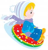 image of inflatable slide  - Little boy or girl sitting in an inflatable snow tube and sliding down - JPG