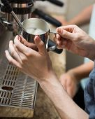 Cropped image of barista steaming milk in coffeeshop