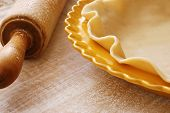 Freshly rolled pie crust (in dish ready to be fluted and filled) with flour dusted vintage rolling pin on wood background.  Macro with shallow dof and copy space.