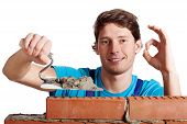 image of putty  - Happy man with putty knife building a brick wall - JPG