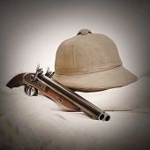 Vintage picture of accessories for safari hunters. Tropical cork helmet and big bore pistol on a animal skin.