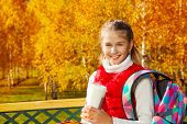foto of 11 year old  - Happy blond 11 years old girl with amazing smile sitting on the bench drinking coffee and wearing backpack in the autumn park on sunny day - JPG
