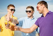 summer, holidays, vacation and happy people concept - group of friends having fun on the beach with bottles of beer or non-alcoholic drinks