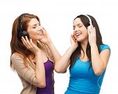 music and technology concept - two smiling teenagers with closed eyes listeting to music with headphones