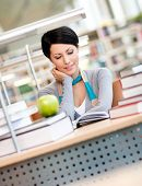 Female student with green apple studies sitting at the desk at the reading hall of the library. Acad