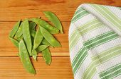 picture of snow peas  - Fresh washed snow peas drying on a rustic wooden table - JPG