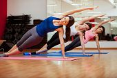 stock photo of yoga  - Group of three young women practicing the side plank pose during yoga class in a gym - JPG