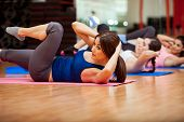 stock photo of rep  - Beautiful young women doing crunches during a class at a gym - JPG