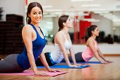stock photo of outfits  - Beautiful young woman trying the cobra pose and smiling during yoga class - JPG