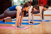 stock photo of yoga  - Beautiful young Hispanic women working out and enjoying their yoga class in a gym - JPG