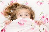 stock photo of dread head  - Little girl having childhood nightmares and fears hiding under the quilt - JPG