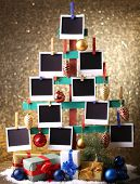 Wooden hand made fir tree with empty photo paper and Christmas decor on shiny background