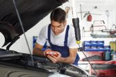 stock photo of car repair shop  - mechanic leaning on bonnet with tester equipment - JPG