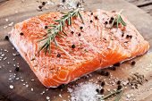stock photo of salmon steak  - Salmon filet with spices on a wooden carving board - JPG