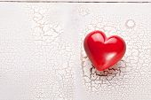 Valentines Day. Red heart on a white craquelure wooden table.