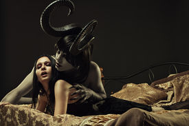 foto of terrific  - Horned horrible demon and gothic girl in bed - JPG