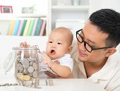 Asian family lifestyle at home. Father and child saving coins to money jar, financial planning conce