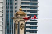 PUTRAJAYA, MALAYSIA - MAY 17, 2014: Pete McLeod of Canada, in an Edge 540 V3 plane flies past the skyscrapers and landmark structures of Putrajaya at the Red Bull Air Race World Championship 2014.