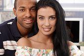 Closeup portrait of beautiful interracial couple smiling at home.