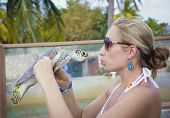 Woman holding and kissing a sea turtle