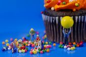 Miniature Plastic People Cleaning Up a Messy Cupcake