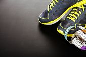 Sport shoes and  measuring tape on grey background