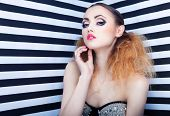 Graphic portrait of beautiful young woman with professional party make up false eyelashes on stripy background