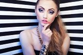 Attractive young woman with eye enlarging make up on stripy background, beauty and fashion concept