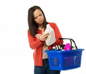Beautiful brunette woman with basket reading label on cleanser