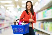 Beautiful cheerful brunette woman with basket full of cleansers in a shop