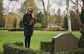 Sad Woman Grieves In A Cemetery Holding Roses