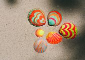 Colorful hand-painted bivalve fan-shaped seashells with bright orange, red, yellow and green stripes arranged neatly on beach sand in a marine themed background, overhead view with copyspace