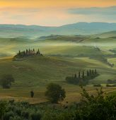Sunrise in a misty valley near Pienza in the Tuscan hills with view on farmhouse