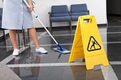 stock photo of janitor  - Maid Cleaning The Floor With Mop In Office - JPG