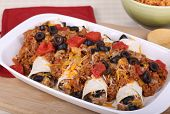 image of enchiladas  - Enchiladas with meat sauce tomatooes and olives on a platter - JPG