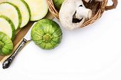 Two Round Zucchini Cut In Slices And Wicker Basket With Vegetables Isolated On White Background