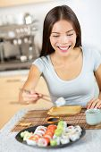 Young pretty asian mixed race asian caucasian model taking healthy lifestyle sushi from plate - about to eat happily smiling looking at food. Sitting at table in kitchen